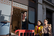 Two Asian girls walk past a construction barrier and a retail poster in central London.