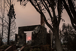 August 1, 2018 - Redding, California, U.S -  The sun sets behind the remnants of a home that burned along the western edge of Redding, California, after the Carr Fire swept through the neighborhood recently. The Carr Fire, which began on July 23, has burned more than 115,000 acres, destroying more than 1,000 residential structures. (Credit Image: © Tracy Barbutes via ZUMA Wire)