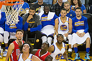 Golden State Warriors forward Draymond Green (23), guard Stephen Curry (30), and guard Klay Thompson (11) watch a NBA preseason game against the Los Angeles Clippers from the bench in the third quarter at Oracle Arena in Oakland, Calif., on October 4, 2016. (Stan Olszewski/Special to S.F. Examiner)