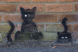 Wokingham, UK. 8th June, 2021. Black cat stencils by a street artist dubbed 'Catsy' by appreciative local residents. There are believed to be around 30-40 such black cat stencils, most of which with stick-on eyes, sprayed around the town by the anonymous street artist.