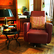 A deep red leather chair on a wooden floor, in front of a mirror and some soft of built-in storage area, a small round black table and lamp with a black shade to its right. There are two square red and gold stripped pillows on the back of the chair for support.