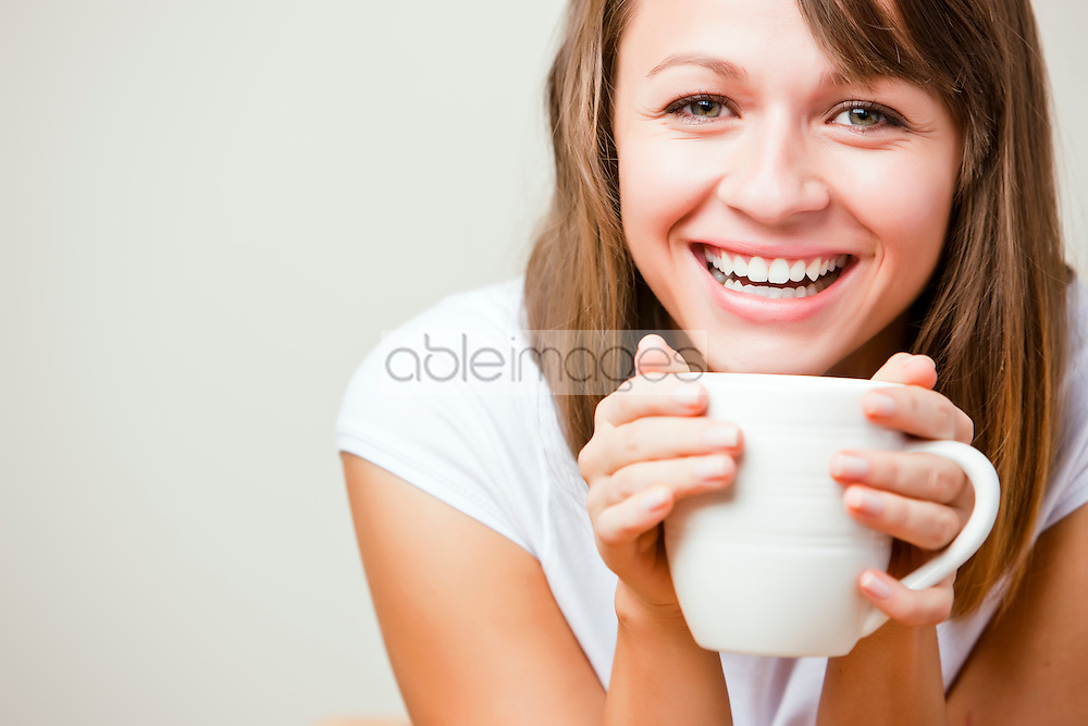 Close up of a smiling young woman holding a mug