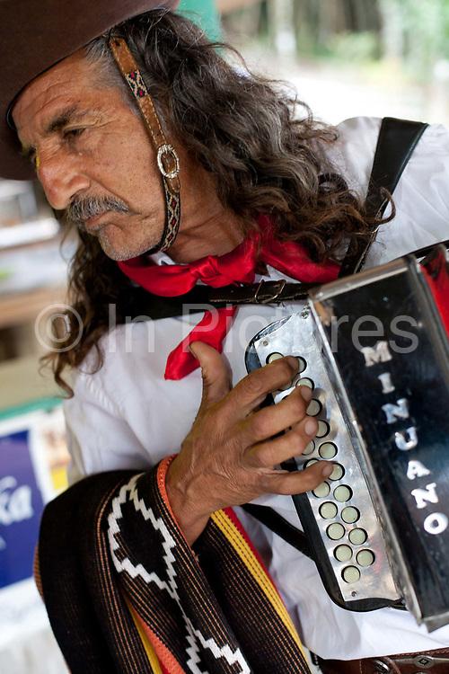 Male Brazilian Gaucho cowboy musician playing accordian. Gaucho cowboy Rodeo, Flores de Cunha, Rio Grande do Sul.