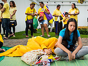 05 DECEMBER 2014 - BANGKOK, THAILAND:  People line up on the sidewalk hoping to catch a glimpse of the motorcade of Bhumibol Adulyadej, the King of Thailand. People wear yellow on the King's Birthday because yellow is considered the King's color. Thais marked the 87th birthday of the King Friday. The revered Monarch was scheduled to make a rare public appearance in the Grand Palace but cancelled at the last minute on the instructions of his doctors. He has been hospitalized in Siriraj Hospital, across the Chao Phraya River from the Palace, since early October.   PHOTO BY JACK KURTZ