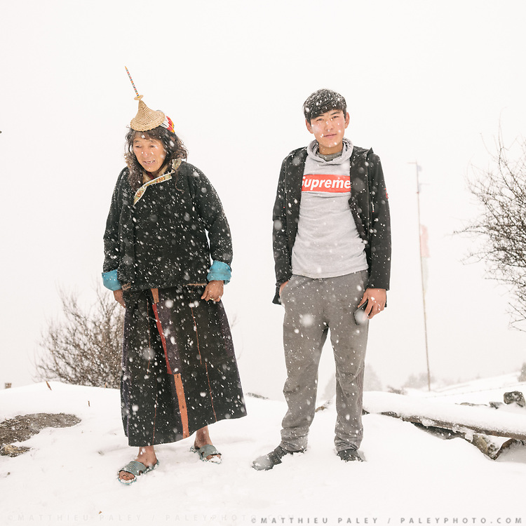 Mother and son pose for a portrait. Son wear a Supreme brand shirt, while mother wears the traditional Laya tibetan outfit.