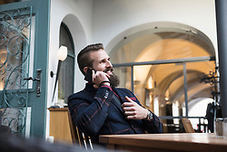 Smiling business man using mobile phone at coffee shop