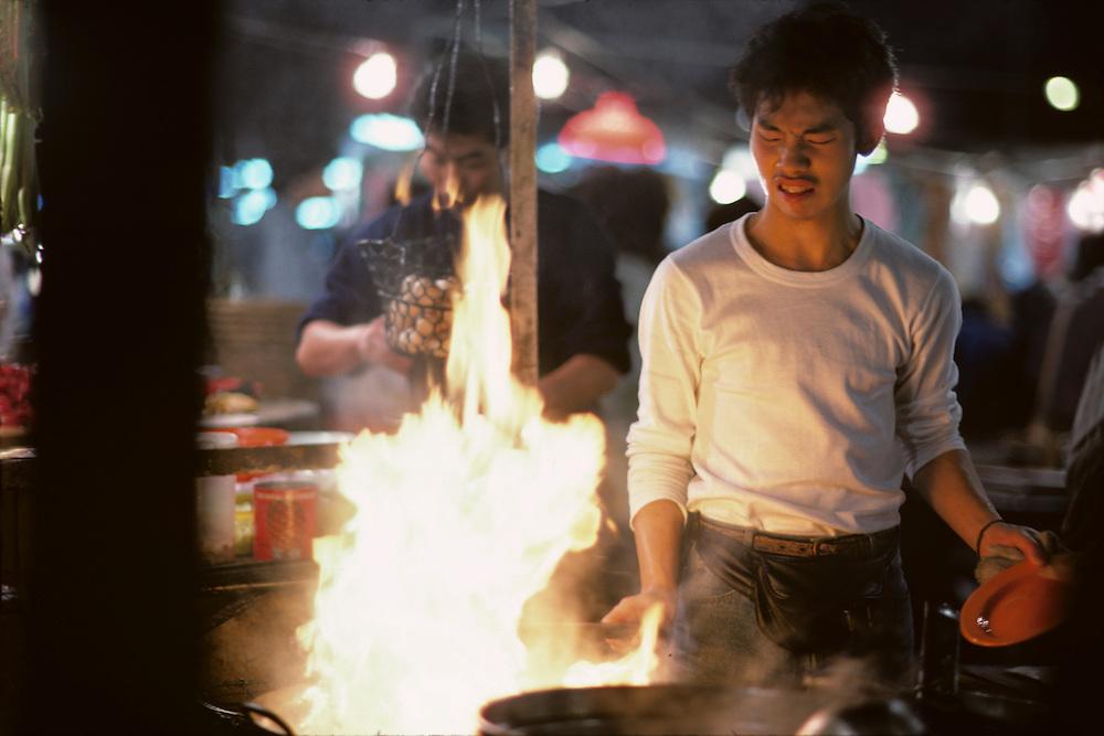 China, Hong Kong, Cook dodges flames at sidewalk cafe in Poor Man's Nightclub