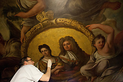 "© Licensed to London News Pictures. 04/03/2013. London, UK. On top of a scaffolding tower at around 40 feet in the air, restoration expert Francesco Rosellini works on gold leaf forming part of a portrait of Queen Anne and her consort Prince George, during restoration work to the ceiling of the 'Painted Hall' at Greenwich Old Naval College in London today (04/03/2013). The conservation work, paid for by the Heritage Lottery Fund (HLF), is the 10th time the Painted Hall (often described as ""finest dining hall in Europe"") will have been restored since its completion in 1784 and will have taken around five months to complete when the hall is unveiled to the public in May of this year. Photo credit: Matt Cetti-Roberts/LNP"