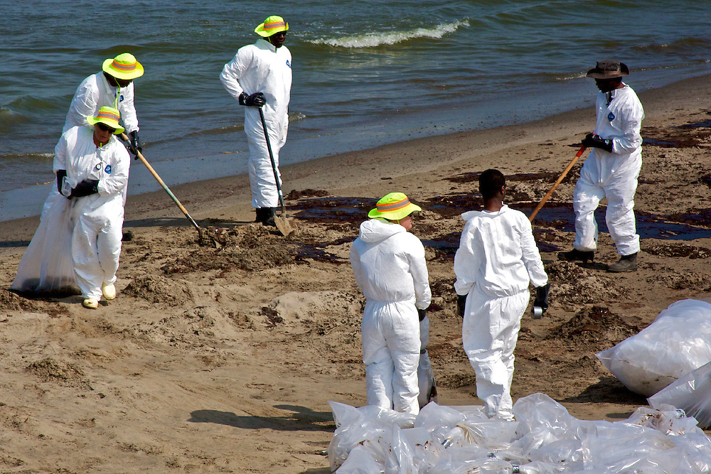 Relief workers shovel oiled sand into plastic bags at Grand Isle State Park, Louisiana, June 5, 2010.
