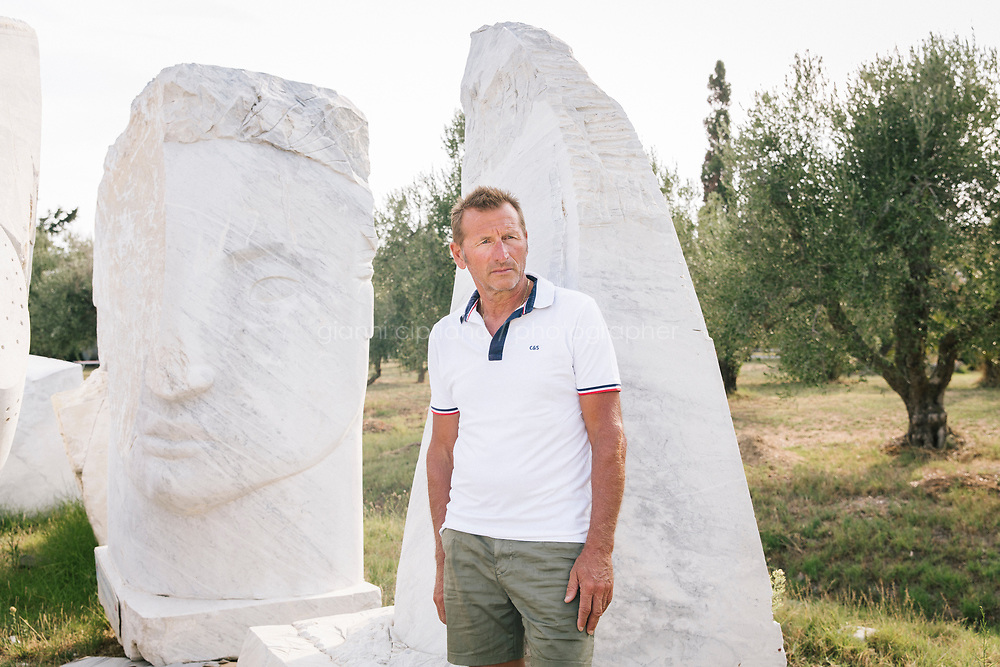 """TALAMONE, ITALY - 26 AUGUST 2019: Fisherman and activist Paolo Fanciulli (58) poses for a portrait in fron of """"The Young Guardian"""", a sculpture by artist Emily Young waiting to be lowered in the sea in Talamone, Italy, on August 26th 2019.<br /> <br /> In 2006, fisherman Paolo Fanciulli used government funds and the donations from his loyal excursion clients to fund a project in which they protected the local waters from trawling by dropping hundreds of concrete blocks around the seabed. But his true dream was to lay down works of art down on the sea floor off the coast of Tuscany. His underwater art dreams came true when the owner of a Carrara quarry, inspired by Mr. Fanciulli's vision, donated a hundred marble blocks to the project.<br /> Mr. Fanciulli invited sculptors to work the marble and set up kickstarter accounts, boat tours and dinners to fund the project. The acclaimed British artist Emily Young carved a ten-ton """"Weeping Guardian"""" face, which was lowered with other sculptures into the water in 2015.<br /> Since then, coral and plant life have covered the sculptures and helped bring back the fish. And Paolo the Fisherman is catching as many of them as he can."""