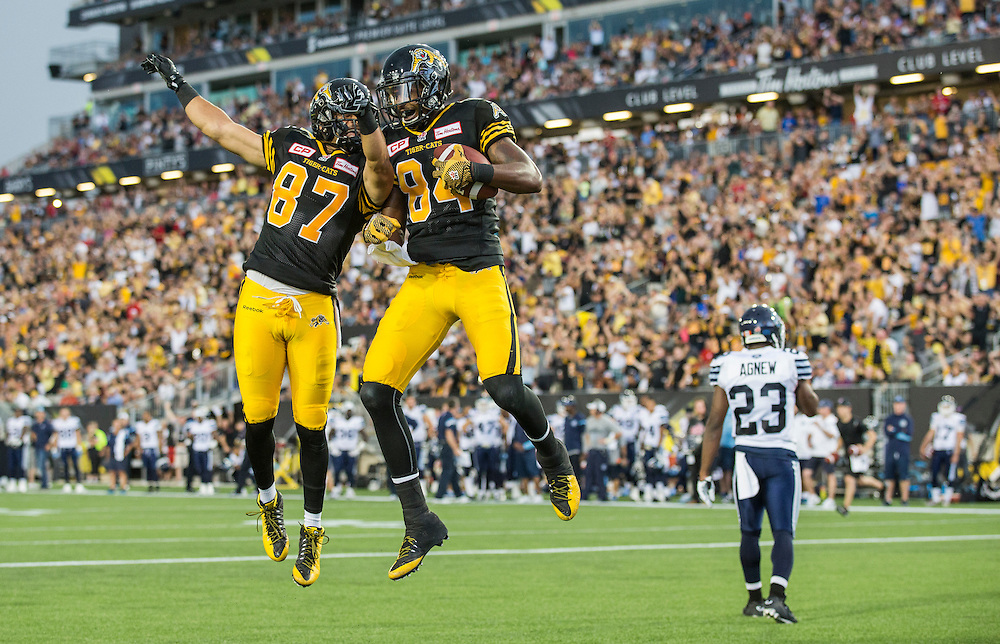 Hamilton Tiger-Cats Bakari Grant (84) celebrates a touchdown with teammate Jasper Collins Jr. against the Toronto Argonauts during the first half of their CFL football game in Hamilton, August 3, 2015.    REUTERS/Mark Blinch