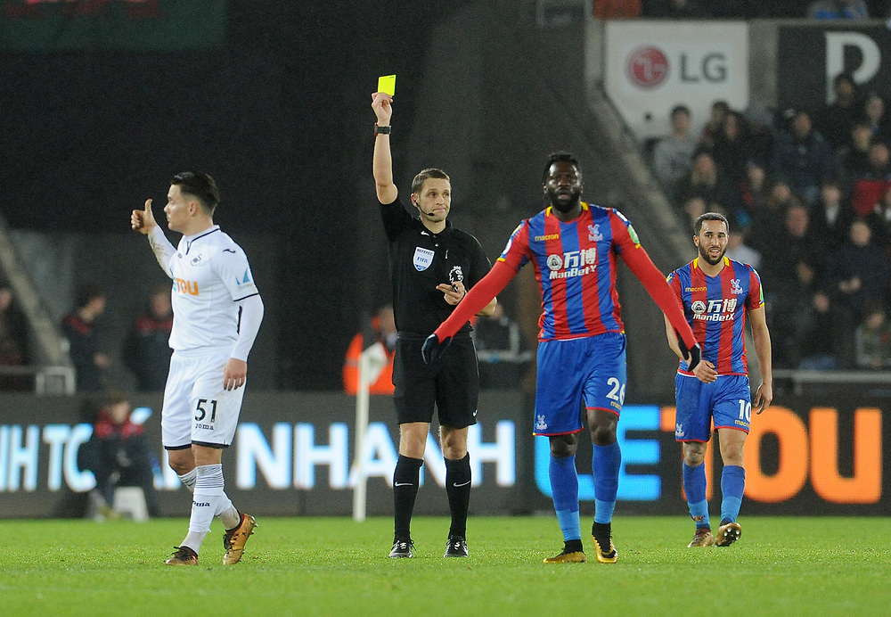 Referee Craig Pawson shows the yellow card to Swansea City's Roque Mesa<br /> <br /> Photographer Ian Cook/CameraSport<br /> <br /> The Premier League - Swansea City v Crystal Palace - Saturday 23rd December 2017 - Liberty Stadium - Swansea<br /> <br /> World Copyright © 2017 CameraSport. All rights reserved. 43 Linden Ave. Countesthorpe. Leicester. England. LE8 5PG - Tel: +44 (0) 116 277 4147 - admin@camerasport.com - www.camerasport.com