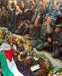 © London News Pictures. FILE PIC DATED 12/11/2004. Ramallah, West Bank.  Palestinian presidential security forces praying on the grave of Yasser Arafat after he was buried in the compound of the Muqaata in the West Bank city of Ramallah.  Scientists are due to exhume the remains of Yasser Arafat in an effort to determine whether his death in 2004 was caused by polonium-210 poisoning.   Photo credit: Grant Fleming/LNP