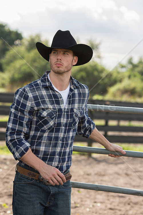 good looking cowboy closing a metal gate on a ranch