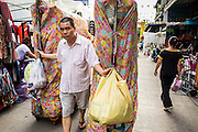 06 JUNE 2013 - BANGKOK, THAILAND:     A man hauls clothes for sale into Bobae Market in Bangkok. Bobae Market is a 30 year old market famous for fashion wholesale and is now very popular with exporters from around the world. Bobae Tower is next to the market and  advertises itself as having 1,300 stalls under one roof and claims to be the largest garment wholesale center in Thailand.       PHOTO BY JACK KURTZ