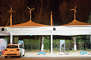 Charging an electric car at night in a motorway service station<br /><br />Electric vehicles are everywhere on China's roads, from battery powered pedal bikes to hybrid cars, electric buses and all types of service vehicles.