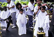 Children and adults having their hair cut for free in a park as part of an NGO's social programme, Rio de Janeiro, Brazil