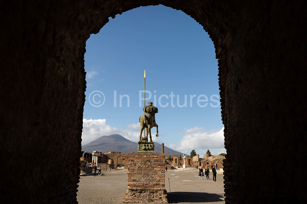People walk past a statue in the almost-deserted Forum at the Pompeii Archeological Park on Friday 6th March 2020 in Pompei, Italy. Park officials estimate that visitor numbers are down to a sixth of what they would normally be as a result of the spread of Coronavirus, which has prompted the closure of all Italian schools and universities, and the postponing of many sporting events. .