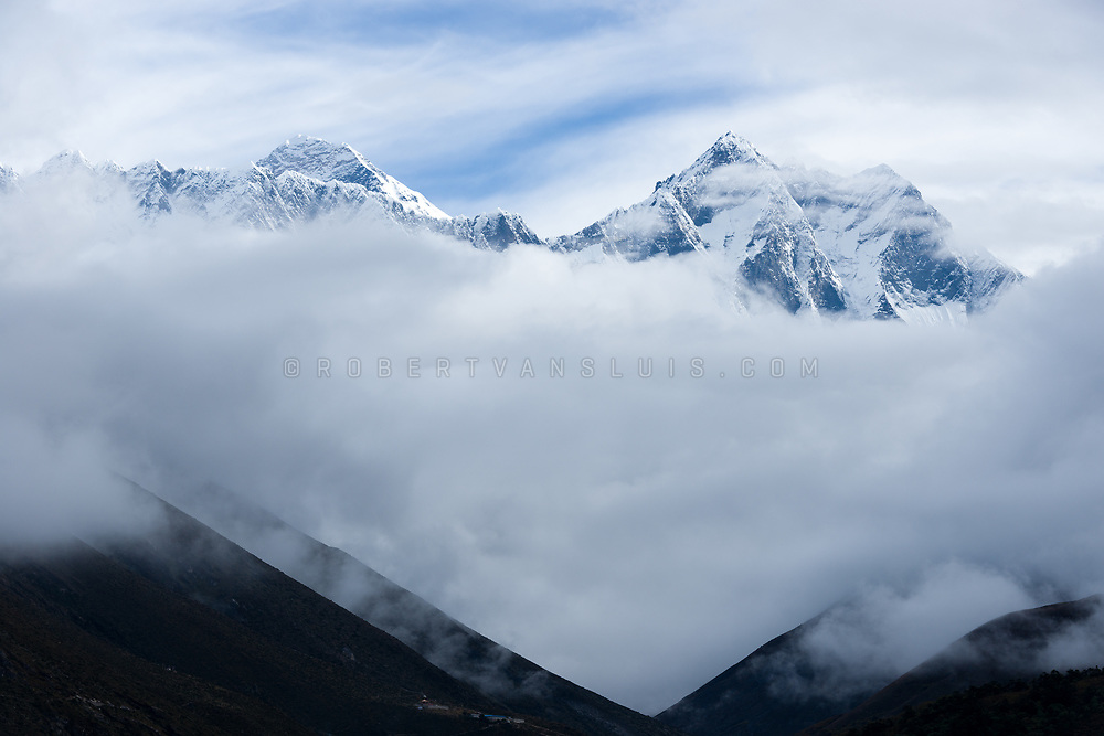 Mount Everest and Lhotse rise above morning clouds, seen from Tengboche, Nepal. Photo © robertvansluis.com