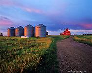 Grain bins and red barn at sunrise near Williston North Dakota