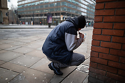 © Licensed to London News Pictures . 25/12/2018 . Manchester , UK . A homeless man cleans his teeth after sleeping rough on Portland Street . Homeless people sleeping rough on the streets of Manchester City Centre on Christmas Day . Photo credit : Joel Goodman/LNP