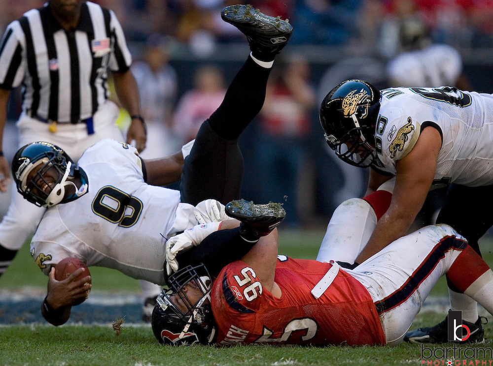 KEVIN BARTRAM/The Daily News.Houston defensive end Jerry Deloach pulls down Jacksonville quarterback David Garrard during the first half on Saturday, Dec. 24, 2005 at Reliant Stadium in Houston. Jacksonville won the game 38-20.