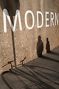 The shadows of pedestrians pass-by the Tate Modern art gallery on the Southbank, on 13th November 2017, in London, England.