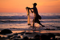 Young man fishing with a throw net at sunset along the coast of Michoacan, Mexico.