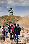 22 APRIL 2003 - SELLS, ARIZONA: Undocumented immigrants under the watch of a US Border Patrol OH-6 helicopter are walked out of the desert on the Tohono O'Odham reservation south of Sells, AZ. The Tohono O'Odham reservation, which spans much of the southern Arizona border with Mexico, was a major crossing point for undocumented immigrants after urban entry points, like Nogales, AZ, and Douglas, AZ, were shut down.          PHOTO BY JACK KURTZ