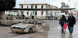 © under license to London News Pictures. 24/02/2011. A family walks by burnt out cars at the Army Compound in Benghazi, Libya. Photo credit should read Michael Graae/London News Pictures