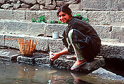 INDIA, KASHMIR a young woman washing dishes on the canal  in Srinager, the capital of Kashmir
