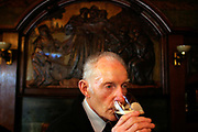 An elderly man drinks his pint of beer in the Blackfriar Public House, London, UK