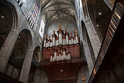Interior of Narbonne Cathedral with its ornate carved organ in Narbonne, France. Cathedrale Saint-Just-et-Saint-Pasteur de Narbonne, is a Gothic style Roman Catholic church located in the town of Narbonne, France. The cathedral is a national monument and dedicated to Saints Justus and Pastor.