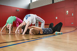 Girls doing bridge position yoga in sports hall, Munich, Bavaria, Germany
