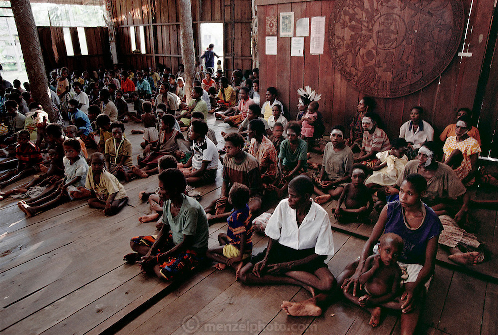Asmattan women in the village of Komor convene to hear the assimilated Catholic and native Good Friday Mass given by one of the local missionaries, Brother Jim, in Komor, Irian Jaya, Indonesia. Men enter through another door and sit on the wooden floor on the other side of the church. The Asmat, on the Arafura Sea, is a large, steamy hot tidal swamp. Image from the book project Man Eating Bugs: The Art and Science of Eating Insects.
