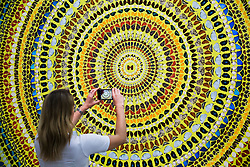"""© Licensed to London News Pictures. 19/09/2019. London, UK. A member of the gallery staff takes a photograph of Damien Hirst's butterflies and household gloss canvas titled """"Cardinal"""" on her phone.<br /> Damien Hirst's first major solo exhibition at White Cube in London in seven years features large-scale concentric butterfly paintings from his new 'Mandalas' series. The 22 works are monumental and vibrant, measuring over 2m x 3m.Photo credit: Dinendra Haria/LNP"""