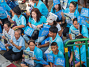 16 AUGUST 2015 - BANGKOK, THAILAND: People sit on a Bangkok street and wait for the ''Ride For Mom'' to start. More than 100,000 people across Thailand participated in the Bike For Mom event in honor of Queen Sirikit, who celebrated her 83rd birthday August 12. In Bangkok, the ride was led by His Royal Highness Crown Prince Maha Vajiralongkorn, the Crown Prince of Thailand and Sirikit's only son. Queen Sirikit, who is in poor health and living in a hospital, was unable to attend the bike ride.     PHOTO BY JACK KURTZ