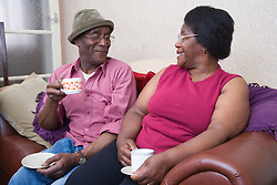 Elderly couple enjoying a cup of tea together,