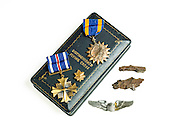 "The Air Medal and the Distinguished Flying Cross awarded to Cpt. Walter Thomason for his exploits over occupied Europe.  Two pieces of ""flak"" are also pictured."