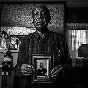 Charles Gilbert, 85, of Aliquippa served in the U.S Army during the Korean War. He has lived in Aliquippa his whole life, and ran track at Aliquippa High School. He holds a photo of his son, Charles Amos Gilbert, who enlisted in the Navy and served in Vietnam after graduating from Aliquippa High School.