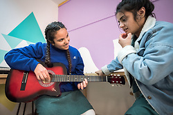 18 February 2020, Amman, Jordan: 15-year-old student Rena Amlaharmeh plays the guitar in the Talent Room of Rufaida Al Aslamieh Primary Mixed School in the Sahab district, with her sixteen-year-old friend Ayyan looking on. The school serves more than 1,000 students from kindergarten up to 10th grade, most of them girls from Jordan but also some from Syria and other countries, and, in the lower grades, also boys. With support from the Lutheran World Federation, the school has refurbished its rooms and buildings and introduced a 'Talent Room' in order to nurture the children's creativity. This type of learning environment is otherwise rare in Jordanian public shools.