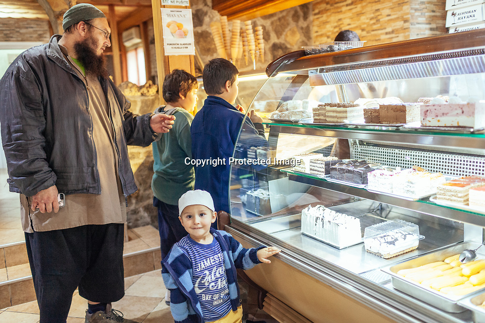 Edis Bosnac and three of his children buy ice cream and cakes in a village neighbouring Gornja Macao, where he lives a secluded life with other members of the religious muslim community.
