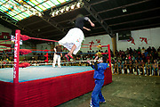 Female wrestler jumping from ropes out of ring onto male opponent with crowd in background. Lucha Libre wrestling origniated in Mexico, but is popular in other latin Amercian countries, including in La Paz / El Alto, Bolivia. Male and female fighters participate in the theatrical staged fights to an adoring crowd of locals and foreigners alike.
