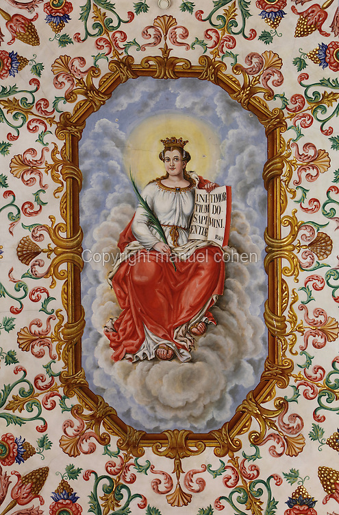 Central medallion of the painted ceiling, with St Catherine of Alexandria representing wisdom and patron saint of students and teachers, 17th century, by Francisco F de Araujo, in the Sao Miguel Chapel, or St Michael's Chapel, designed in Manueline style 1517-22 by Marco Pires and completed by Diogo de Castilho, on the site of a 12th century chapel in the University of Coimbra, Coimbra, Portugal. The chapel was renovated in the 17th and 18th centuries, with pulpit built by Manuel Ramos in 1684, tiled floor added 1613, Baroque organ with 2,000 pipes built 1733 by Fray Manuel de Sao Bento, chinoiserie painting by Gabriel Ferreira da Cunha in 1737, and Mannerist altarpiece designed by Bernardo Coelho in 1605 and made by sculptor Simon Mota, with paintings by Simon Rodrigues and Domingos Vieira Serrao. The University of Coimbra was first founded in 1290 and moved to Coimbra in 1308 and to the royal palace in 1537. The building is listed as a historic monument and a UNESCO World Heritage Site. Picture by Manuel Cohen