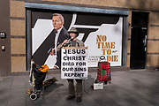 A Christian man who frequents the West End carrying religious messages from the Bible, stands in front of a poster for Daniel Craigs last appearance as James Bond in the film Not a Day to Die, which has finally opened around the country, delayed after the Covid pandemic, on 12th October 2021, in London, England.