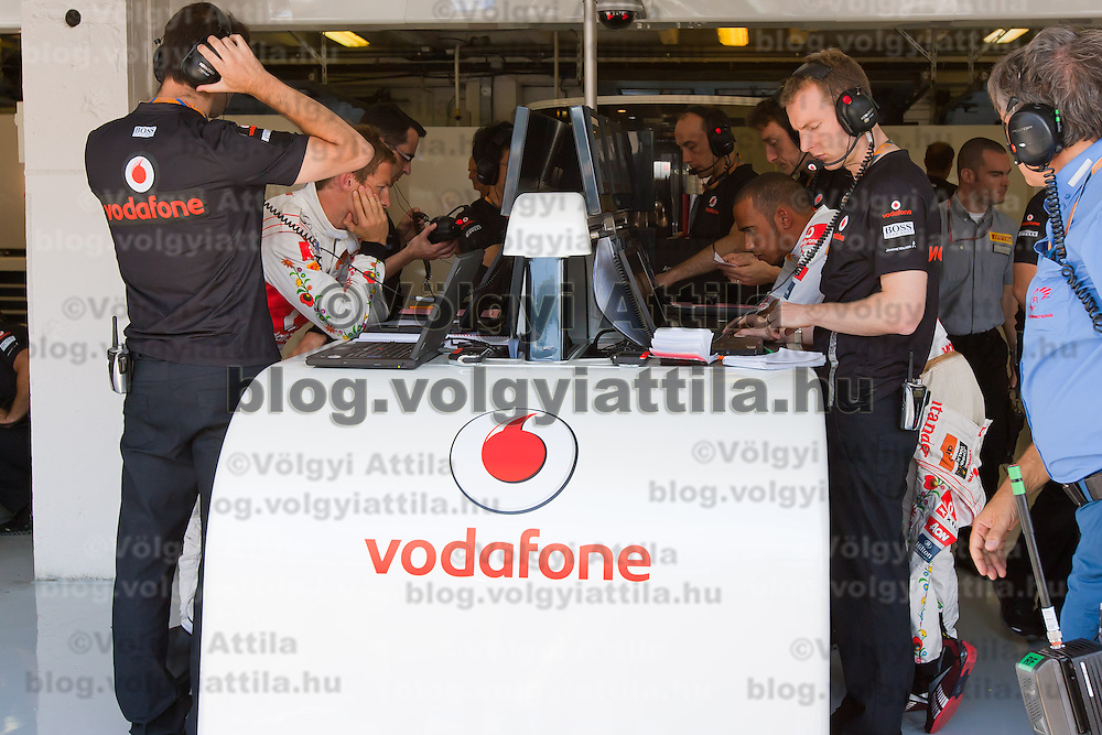McLaren Formula One drivers Jenson Button (2nd L) and Lewis Hamilton (2nd R) of Britain check their results both wearing a Kalocsa design outfit after the free practice of the Hungarian F1 Grand Prix in Mogyorod (about 20km north-east from Budapest), Hungary. Saturday, 30. July 2011. ATTILA VOLGYI.Team sponsor Hugo Boss celebrates its 30th anniversary with special fan made designs for competition saturdays on all races. On Hungaroring the special design is from Hungarian folk tradition with motives from Kalocsa..