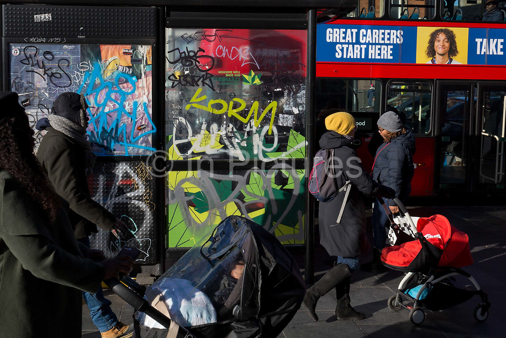 Mothers push cilds buggies past a career bus ad and a graffiti-covered bus stop in Brixton, on 30th january 2019, in Lambeth, south London, England.