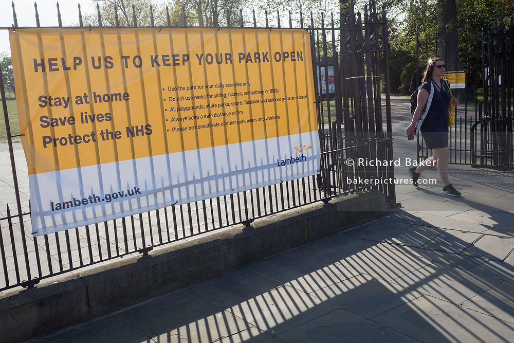 As the UK government's lockdown restrictions during the Coronavirus pandemic continues, and number of UK reported cases rose to 138,078 with a total now of 18,738 deaths, a Londoner passes a banner by Lambeth Council advising on social distancing restrictions and overall behaviour has been stretched across the gates of Brockwell Park, a public green space in the south London borough of Lambeth, on 23rd April 2020, in London, England.