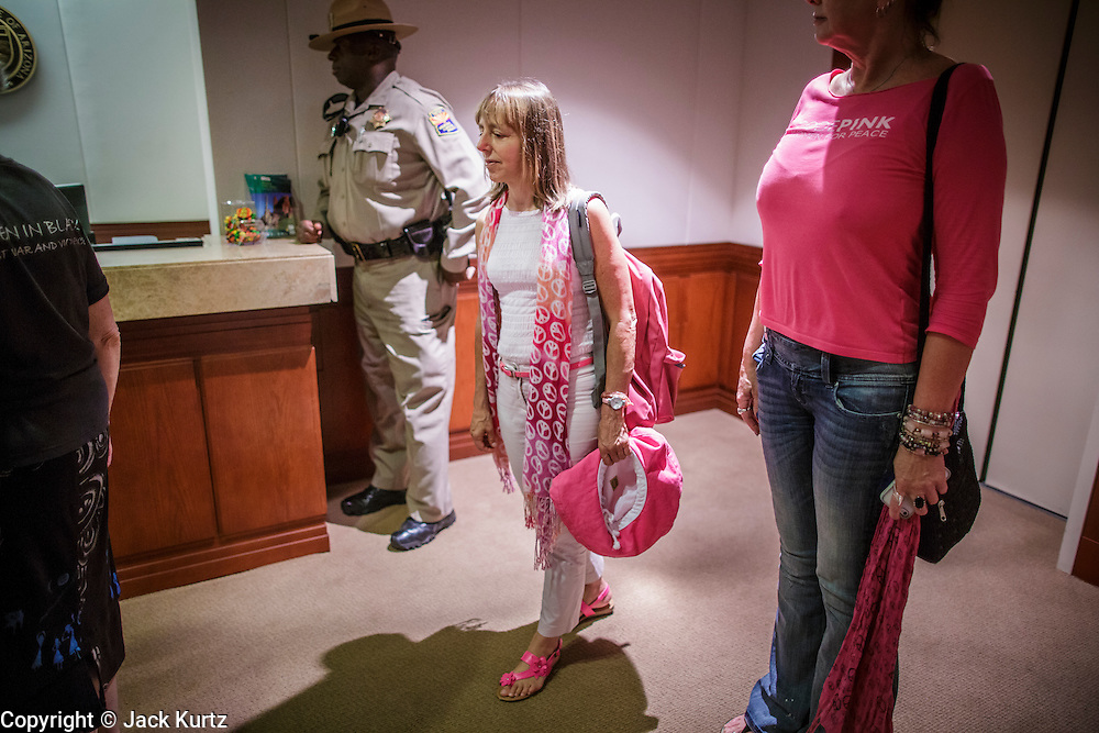 "31 JULY 2012 - PHOENIX, AZ:  MEDEA BENJAMIN, center, and other members of Code Pink, accompanied by an Arizona State Trooper, wait in the lobby of the governor's office at the Arizona State Capitol Tuesday. Medea is a political activist, best known for co-founding Code Pink and, along with her husband, activist and author Kevin Danaher, the fair trade advocacy group Global Exchange. She was also a Green Party candidate in 2000 for the United States Senate. She appeared in Phoenix to promote her new book, ""Drone Warfare: Killing by Remote Control."" She, and other members of Code Pink, presented a letter to Arizona Gov. Jan Brewer protesting Brewer's request to use the state's airspace to train drone pilots.  PHOTO BY JACK KURTZ"