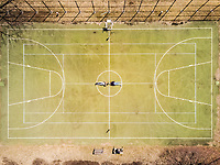 Aerial view of two people lying on a basket/ Tennis ground in Singapore.